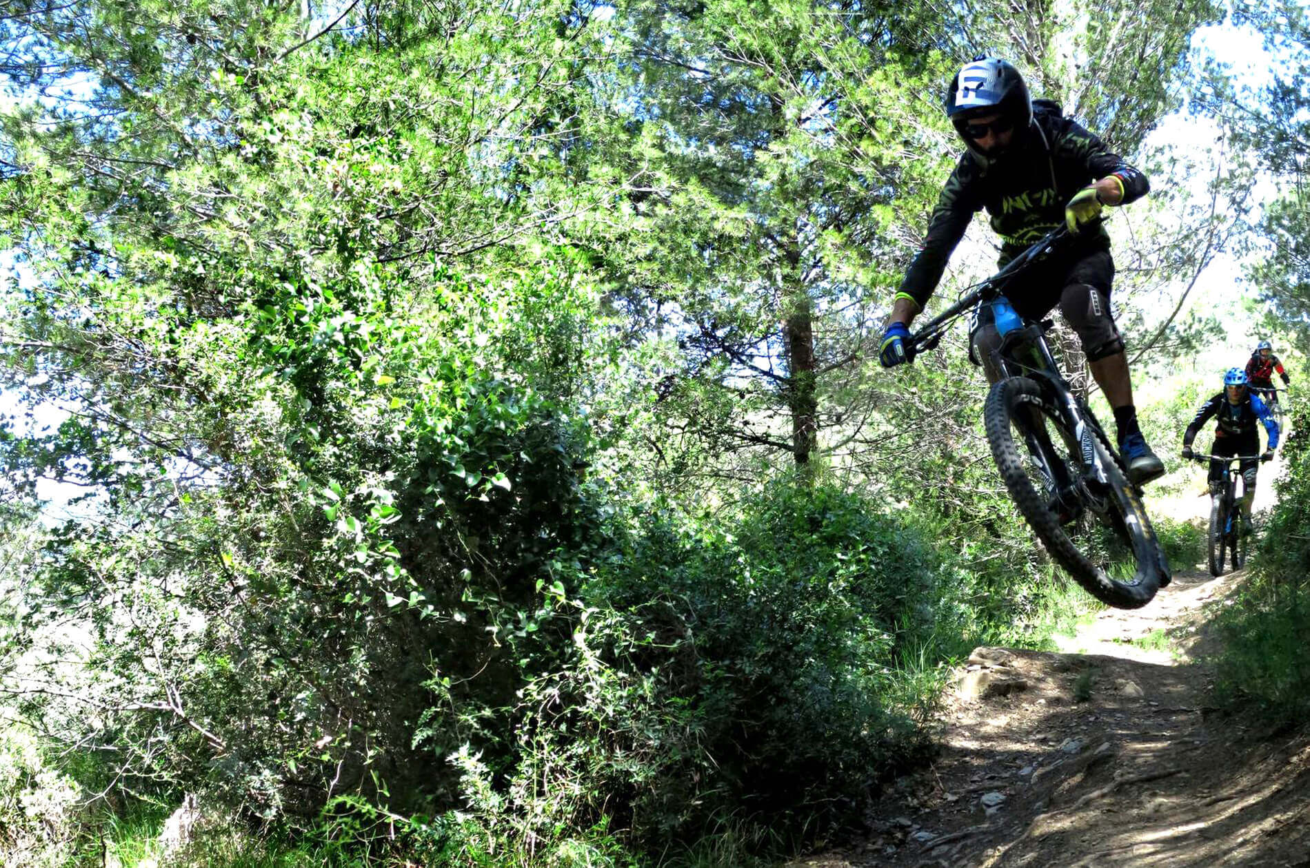 Bikers on mountain bike downhill in the green Ligurian hills
