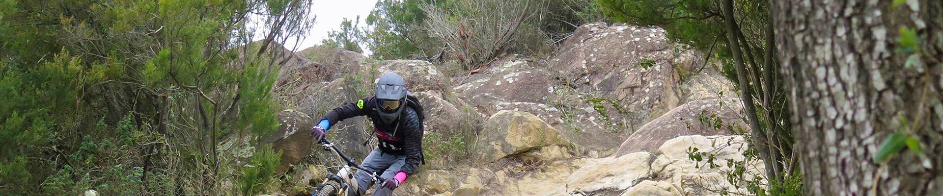 Biker downhill between rocks and slopes